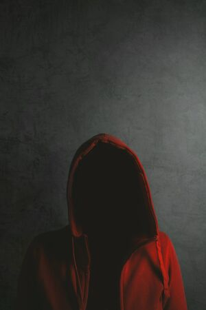 hooded shirt: Unrecognizable person wearing red hooded shirt, low key portrit in dark room