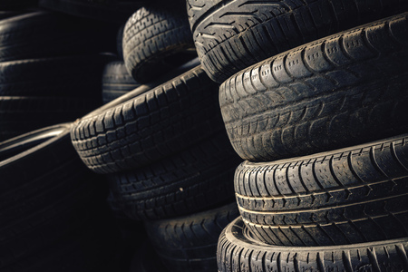 차 자동차 부품 가게 차고에서 사용하는 오래 된 자동차 타이어의 열 스택입니다. 스톡 콘텐츠
