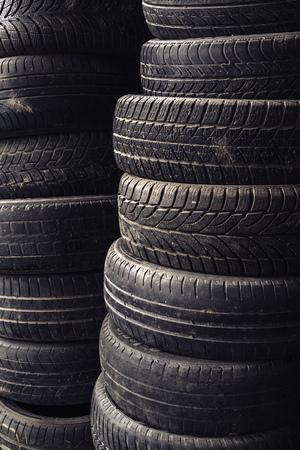 pneumatic tyres: Column stack of old used car tires in secondary car parts shop garage.