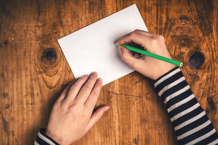 comunicación escrita: Mujer que escribe la dirección del destinatario en el sobre de envío, las manos femeninas desde arriba en el escritorio de oficina de envío de la carta, vista desde arriba, retro tonos.