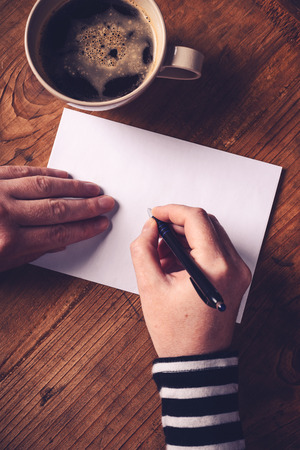 penfriend: Woman drinking coffee and writing letters, top view of female hands writing recipient address on white envelope, retro toned image with selective focus.