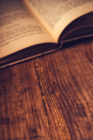 Old book wooden library desk with unreadable text, retro toned image, selective focus