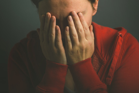 sorrowful: Sorrowful woman crying in despair, low key portrait of adult female in tears, covering face with her hands Stock Photo