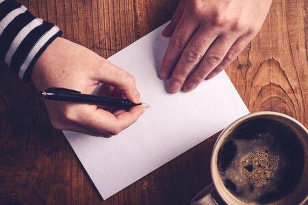 letter envelopes: Mujer de tomar caf� y escribir cartas, vista desde arriba de las manos femeninas escribir la direcci�n del destinatario en el sobre blanco, tonos retro imagen con enfoque selectivo.