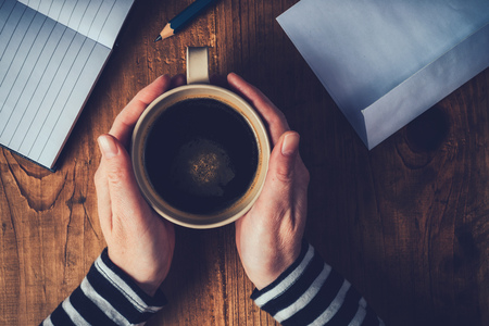 penfriend: Woman drinking coffee and writing letters, top view of female hands with coffee cup, retro toned image with selective focus.