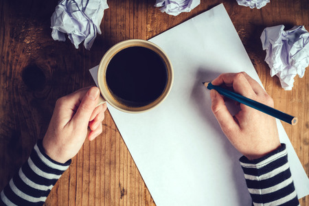 Female scrittore bere tazza di caffè, vista dall'alto di mani femminile azienda tazza di caffè sopra matite e carta su una scrivania, immagine retrò tonica. Archivio Fotografico - 50260219