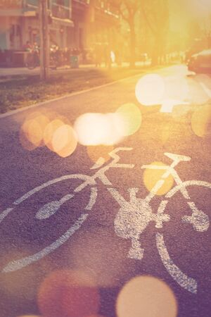 road mark: Retro toned bicycle lane mark on the street in sunset, selective focus with lens flare and bokeh light