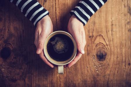 tomando café: Mujer sola de tomar café en la mañana, vista desde arriba de las manos femeninas que sostienen la taza de bebida caliente en la mesa de madera, tonos retro.