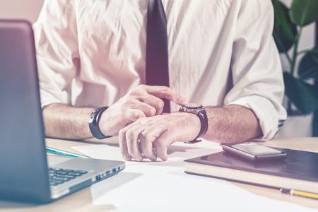 trabajo: El hombre de negocios que controla el tiempo en el reloj, las horas extraordinarias de trabajo en el escritorio de la oficina, la multitarea y el concepto de plazo del proyecto, imagen retro tonos, enfoque selectivo Foto de archivo