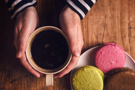 hot drinks: Coffee and macaron cookies on table , female hand holding cup with hot beverage, top view, retro toned