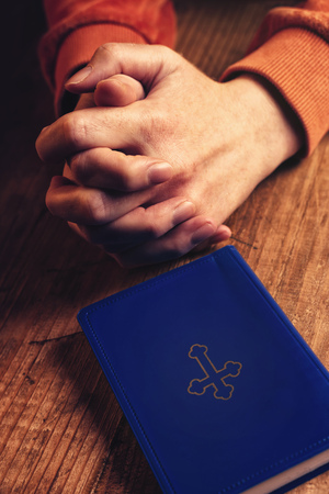 mani incrociate: donna cristiana che prega con le mani incrociate e Sacra Bibbia al suo fianco sulla scrivania di legno in chiesa Archivio Fotografico