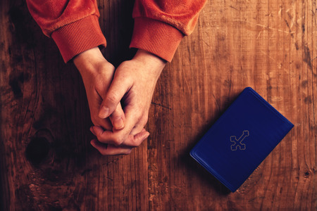 pray: Christian woman praying with hands folded and fingers crossed, Holy Bible by her side on wooden desk in church, top view