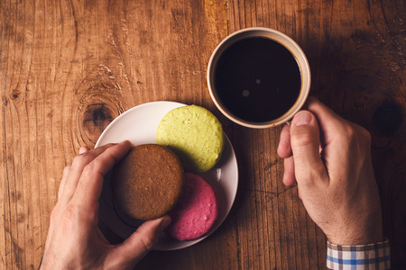 coffee table: Macaron cookies and coffee on table in the morning, male hands holding cup with hot beverage and sweet biscuit, top view, retro toned