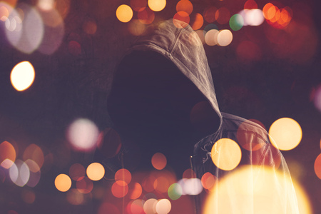 Faceless unknown and unrecognizable person without identity wearing hooded shirt, retro toned image with bokeh light