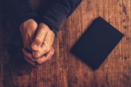 catholic church: Christian man praying with hands crossed and Holy Bible by his side on wooden desk in church, top view