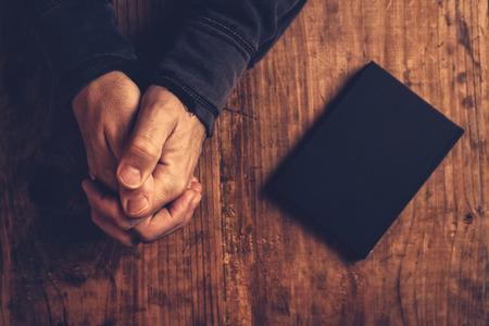 mani incrociate: cristiano che prega con le mani incrociate e Sacra Bibbia al suo fianco sulla scrivania di legno in chiesa, vista dall'alto Archivio Fotografico
