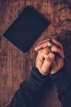 church: Manos plegables del hombre cristiano que ruega con la Santa Biblia a su lado en la mesa de madera en la iglesia, vista desde arriba