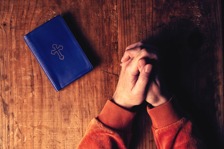 Christian woman praying with hands crossed and Holy Bible by her side on wooden desk in church, top view Stock Photo