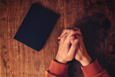 Handen van de christelijke vrouw bidden met Heilige Bijbel aan haar zijde op houten bureau in de kerk, bovenaanzicht