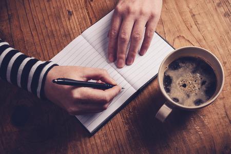 커피를 마시고 일기 메모를 작성하는 여성, 노트북, 선택적 포커스가있는 레트로 톤된 이미지를 작성하는 여성 손의 상위 뷰. 스톡 콘텐츠