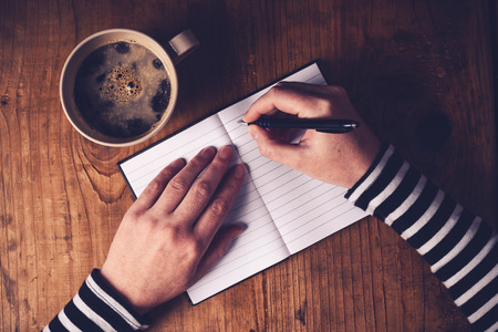 publicist: Woman drinking coffee and making a diary note, top view of female hands writing in notebook, retro toned image with selective focus.