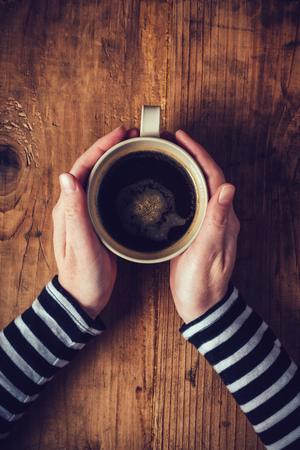 아침에 커피를 마시는 외로운 여자, 나무 책상에 뜨거운 음료 컵을 들고 여성의 손의 평면도, 복고 톤.