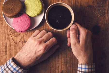 male hand: Coffee and macaron cookies, male hand holding cup with hot beverage, top view, retro toned