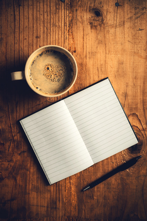 Top view of open notebook with blank pages, writing pencil and cup of coffee on old wooden desk, retro toned image Foto de archivo