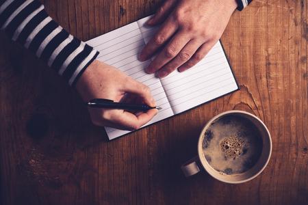 napsat: Žena pití kávy a dělat deník poznámku, pohled shora ženské ruce psaní v notebooku, retro tónovaný obraz s selektivní zaměření.