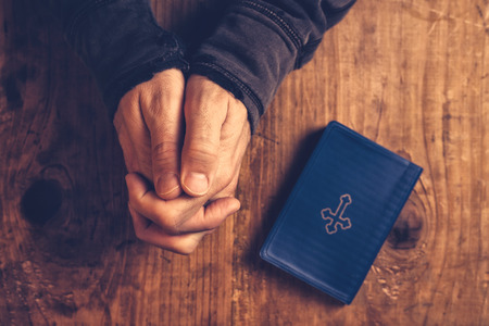hand of god: Christian man praying with hands folded and fingers crossed with Holy Bible by his side on wooden desk in church, top view