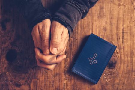 mani incrociate: cristiano che prega con le mani giunte e le dita incrociate con Sacra Bibbia al suo fianco sulla scrivania di legno in chiesa, vista dall'alto Archivio Fotografico