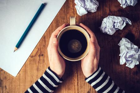 커피의 여성 작가 마시는 컵, 책상, 복고 톤 이미지에 연필과 종이 위의 커피 잔을 들고 여성의 손의 평면도.