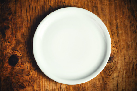 plato de comida: Empty white dinner plate on rustic wooden kitchen table, top view