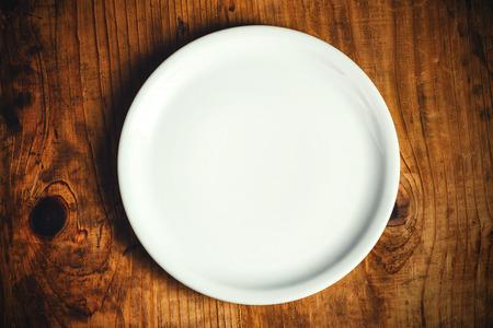 plato de comida: Vac�o plato blanco sobre la mesa de la cocina r�stica de madera, vista desde arriba