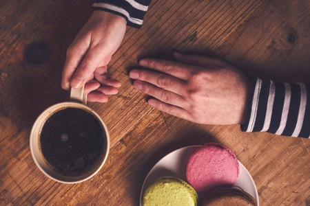 ordinary: Coffee and macaron cookies, female hand holding cup with hot beverage, top view, retro toned
