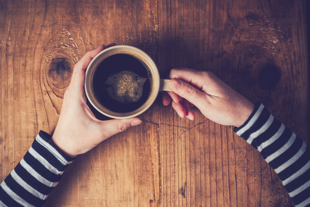 hand hold: Lonely woman drinking coffee in the morning, top view of female hands holding cup of hot beverage on wooden desk, retro toned.