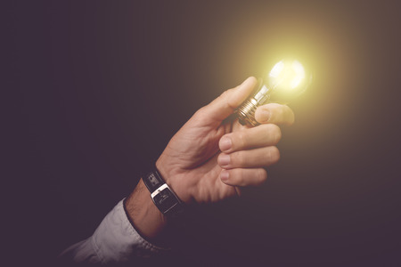 ingenious: Businessman holding light bulb, concept of new ideas, business innovation and creativity, retro toned image, selective focus.