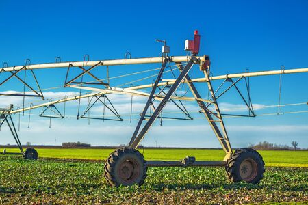 machinery machine: Automated farming irrigation sprinklers on cultivated field