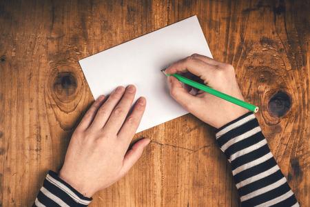 Mujer que escribe la dirección del destinatario en el sobre de envío, las manos femeninas desde arriba en el escritorio de oficina de envío de la carta, vista desde arriba, retro tonos.