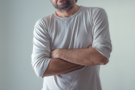 insecurity: Casual ordinary man in blank white shirt with arms crossed, standing on plain gray background, body language. Stock Photo