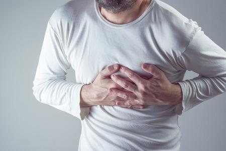 dolor de pecho: dolores de cabeza severos, el hombre que sufre de dolor de pecho, infarto de miocardio o tener calambres dolorosos, presionando sobre el pecho con la expresión dolorosa. Foto de archivo