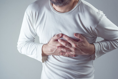 muscle spasm: Severe heartache, man suffering from chest pain, having heart attack or painful cramps, pressing on chest with painful expression.