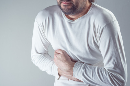 cramps: Severe abdominal pain, man suffering from stomach ache, holding his belly and having painful cramps.