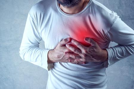 dolor de pecho: dolores de cabeza severos, el hombre que sufre de dolor de pecho, infarto de miocardio o tener calambres dolorosos, presionando sobre el pecho con la expresi�n dolorosa. Foto de archivo
