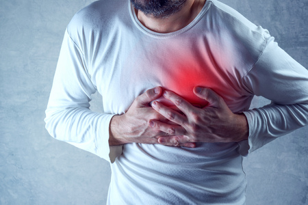 human chest: Severe heartache, man suffering from chest pain, having heart attack or painful cramps, pressing on chest with painful expression.