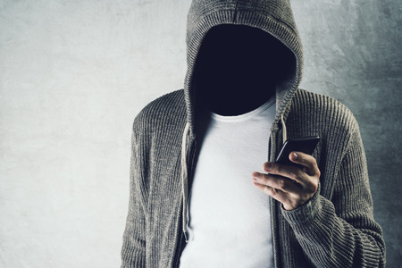 携帯電話、スマート フォン、認識できない男性を使用して顔の見えないフード付き人アイデンティティの盗難やテクノロジー犯罪概念。