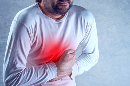convulsion: dolor abdominal intenso, el hombre que sufre de dolor de estómago, la celebración de su vientre y tener calambres dolorosos. Foto de archivo