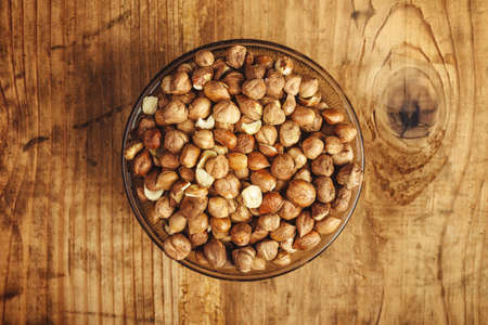 plenty: Plenty of ripe hazelnuts in bowl, healthy edible organic hazel nuts on kitchen table, top view with selective focus Stock Photo