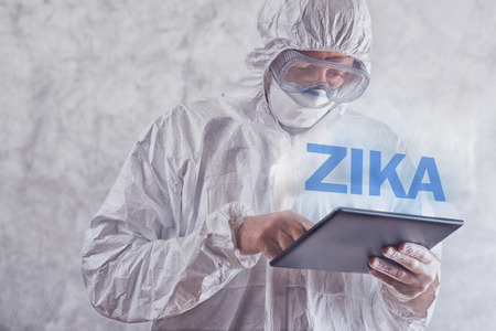 protective: Zika virus concept, medical worker in protective clothes using digital tablet computer to access internet and study symptoms, diagnosis and treatment of this illness. Stock Photo