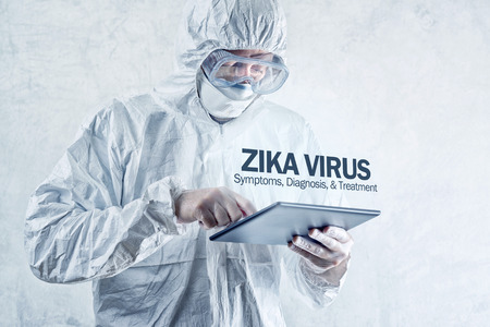 incubation: Zika virus concept, medical worker in protective clothes using digital tablet computer to access internet and study symptoms, diagnosis and treatment of this illness. Stock Photo